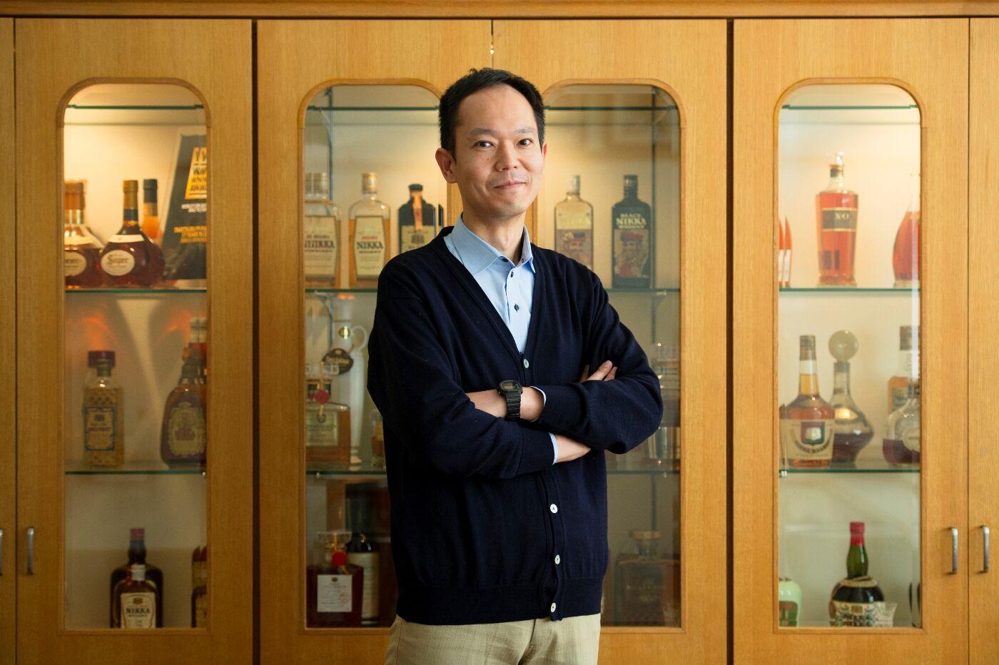 ウイスキー陳列棚の前に立つ綿貫氏の写真