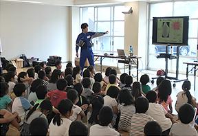 子どもに向けた環境教育の様子、小学校に出向き話をする研究員